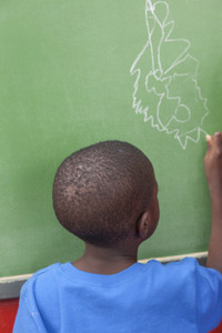 The boy drawing at the blackboard