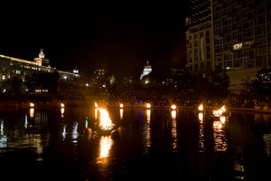 The burning bowls of fire set on the river during the annual WaterFire event in Providence Rhode Island.  In the background is the famous capital building.