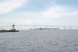 The Newport Rhode Island area Claiborne Pell bridge as seen from a distance on a hazy day along with the lighthouse on Goat Island.  The 70th longest suspension bridge in the world.