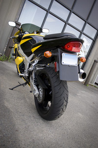 The rear view of a modern yellow motorcycle.