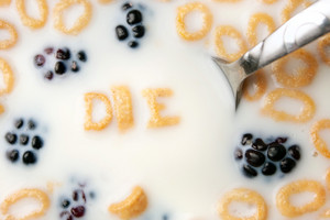 The word DIE spelled out of letter shaped cereal pieces floating in a milk filled cereal bowl.