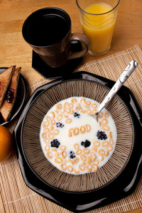 The word FOOD spelled out of letter shaped cereal pieces floating in a milk filled cereal bowl. Surrounding is an orange juice coffee and toast with jelly.