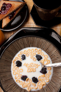 The words HAPPY DAY spelled out of letter shaped cereal pieces floating in a milk filled cereal bowl.