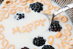 The words HAPPY spelled out of letter shaped cereal pieces floating in a milk filled cereal bowl.