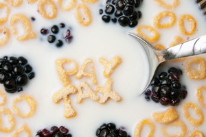 The words PAY TAX spelled out of letter shaped cereal pieces floating in a milk filled cereal bowl.