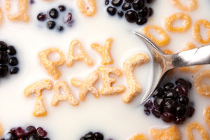 The words PAY TAXES spelled out of letter shaped cereal pieces floating in a milk filled cereal bowl.