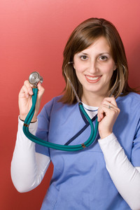 This nurse is holding up her stethoscope and smiling.