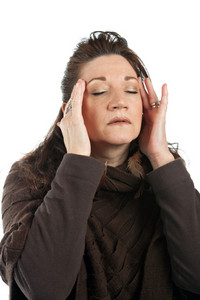 This woman has a stressed out look on her face while holding her hands on her head and temples.