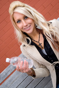This young blonde female is holding a bottle of water.