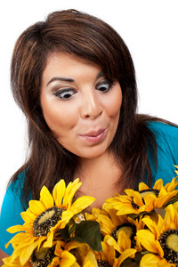 This young hispanic woman looks totally and completely surprised by this bouquet of sun flowers.