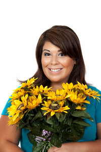 This young smiling hispanic woman looks totally and completely pleased with this bouquet of sunflowers.