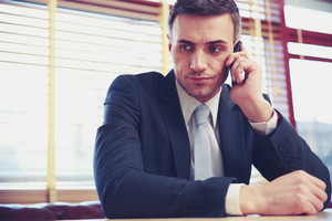 Thoughtful businessman sitting and talking on the phone at office