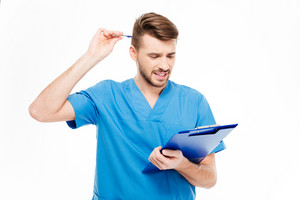 Thoughtful male doctor standing with clipboard isolated on a white background
