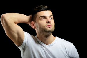 Thoughtful male model posing on a black background