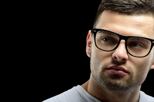 Thoughtful young guy with glasses in front of a dark background