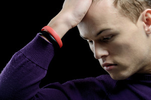Thoughtful young man with his hand on his forehead on dark background