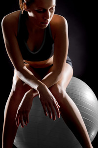 Thoughtful young woman relaxing on fitness ball on black background