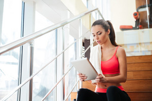 Thougtful pretty young sportswoman using tablet after training in gym