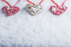 Three beautiful romantic vintage hearts are hanging on a red band on a white snow winter background. Love and St. Valentines Day concept.