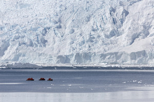 Three boats traveling past a large iceberg