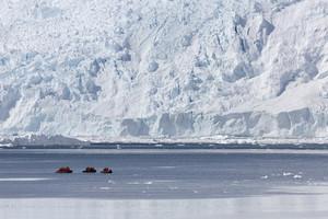 Three boats traveling past a large iceberg