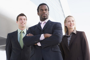 Three business people standing outdoors by building smiling