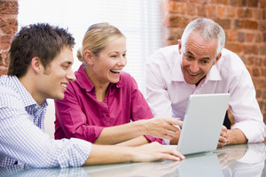 Three businesspeople in office with laptop pointing and laughing