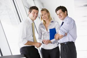 Three businesspeople standing in corridor smiling