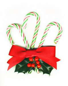Three Candy Canes Tied With A Red Ribbon And With A Holly Sprig.