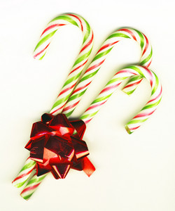 Three Candy Canes With Red Bow On White Background Isolated