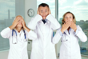 Three clinicians in white coats covering eyes