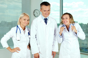 Three clinicians in white coats looking at camera with funny expression