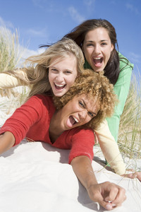 Three female friends having fun and laughing at beach