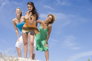 Three female friends relaxing at beach against blue sky