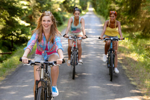 Three female friends riding bikes in park enjoy summer sport