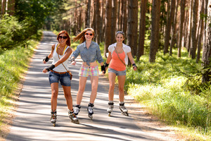 Three friends on in-line skates outdoor on summer countryside road