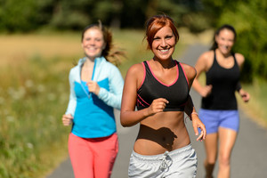 Three friends running outdoors on sunny day smiling