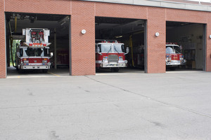Three garage bays of fire house open with firetrucks on disply.