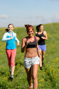 Three girls jogging downhill summer meadow and smiling