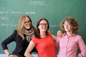 Three happy schoolgirls with glasses