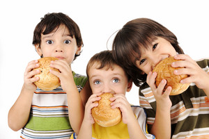 Three kids eating burgers