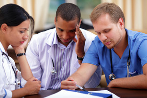 Three medical doctors brainstorming in hospital