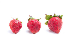 Three red strawberries isolated over white.  Shallow depth of field.