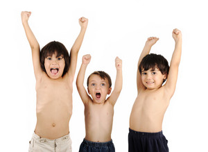 Three shirtless kids celebrating