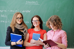 Three smiling schoolgirls holding books