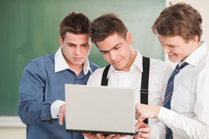 Three students looking at a laptop in a classroom