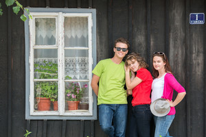 Three teenagers standing in front of wooden house