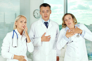 Three unpleasantly surprised clinicians in white coats looking at camera