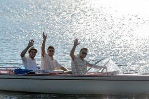 Three waving young men silhouette driving powerboat