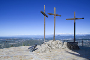 Three wooden crosses on a viewing podium atop a mountain